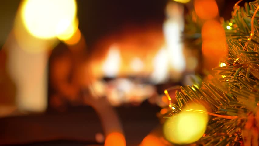 Put a gift on the table. Christmas three on glow fireplace bokeh lights background | Shutterstock HD Video #1020885835