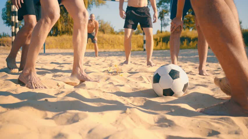 Sport Soccer players in dynamic action funny play on the sand in beach football in summer sunny day under sunlight.