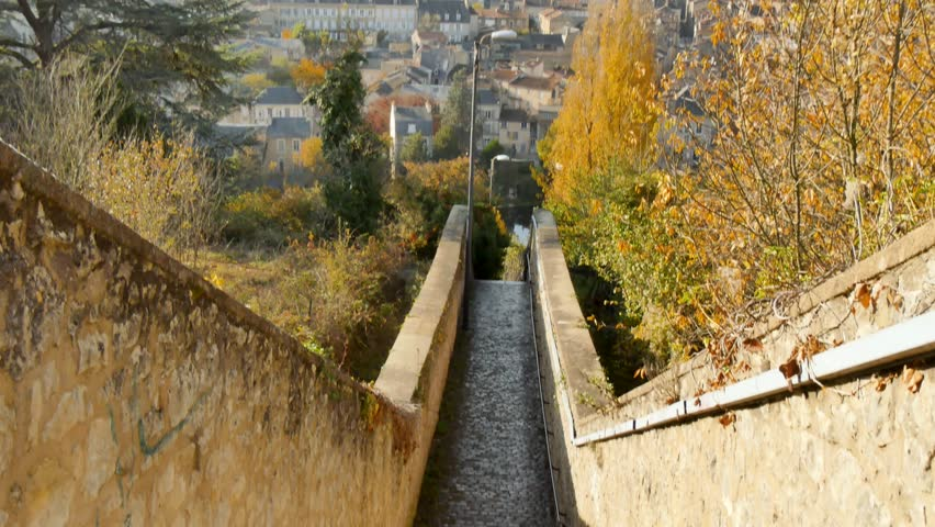 View of the city of Poitiers in the Vienne department, France. Camera movement. It starts with a view of the stairs and goes up to a panorama of the city in the background. Filmed during the fall. | Shutterstock HD Video #1020901165