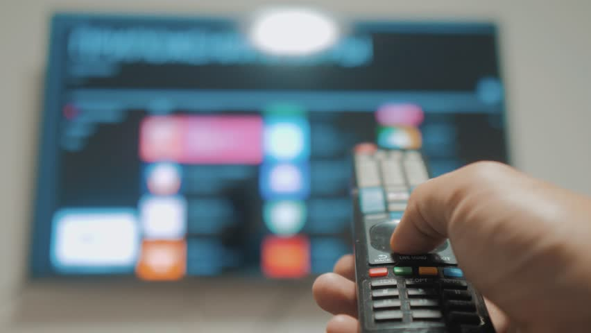 Smart tv with apps and hand. Male hand holding the remote control turn off smart tv . man hand lifestyle controls TV holding remote. TV concept internet online cinema | Shutterstock HD Video #1020911095