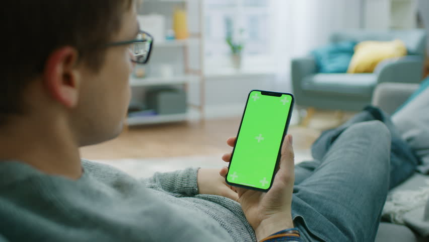 Man at Home Resting on a Couch using Smartphone with Green Mock-up Screen, Doing Swiping, Scrolling Gestures. Guy Using Mobile Phone, Internet Social Networks Browsing. | Shutterstock HD Video #1020934105