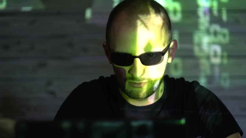 A man hacker man in sunglasses in a dark room works with the program code   Shutterstock HD Video #1020939235
