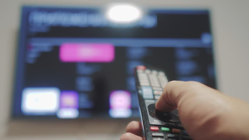 Smart tv with apps and hand. Male hand holding the remote control turn lifestyle off smart tv . man hand controls TV holding remote. TV concept internet online cinema | Shutterstock HD Video #1021006255