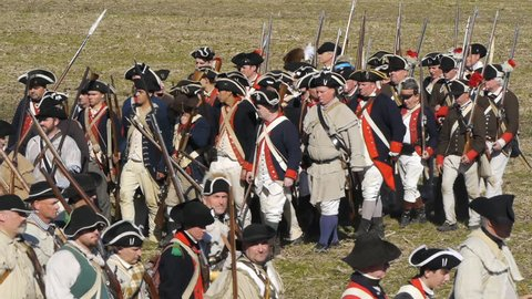 VIRGINIA - OCTOBER 2018 - Reenactment, large-scale, epic American Revolutionary War anniversary recreation -- U.S. Continental Army Soldiers in formation marching as on parade with Muskets, flags.