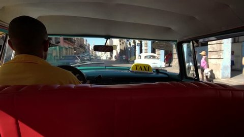 Taxi driver in classic American 1950's vintage car drive on famous street in old Havana neighborhood, Cuba