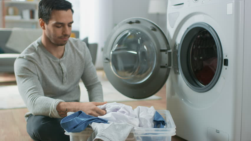 Handsome Smiling Young Man in Grey Jeans and Shirt Sits in Front of a Washing Machine at Home. He Loads the Washer with Dirty Laundry. Bright and Spacious Living Room with Modern Interior. | Shutterstock HD Video #1021113505