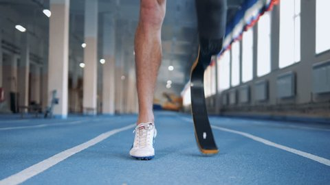 Close up of a male artificial leg being warmed up before jogging