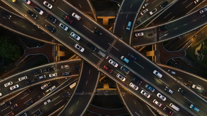 Rising drone shot reveals spectacular elevated highway and convergence of roads, bridges, viaducts in Shanghai at night, transportation and infrastructure development in urban China #1021117075