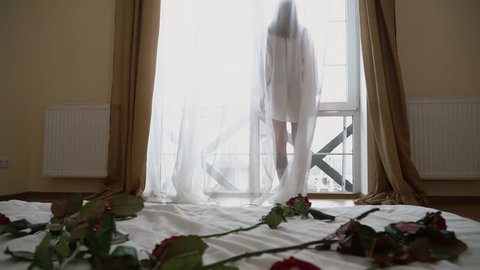 Pretty young woman in short transparent shirt standing near a large bright window. Girl in nightie looks out the window while standing in the bedroom in the morning.