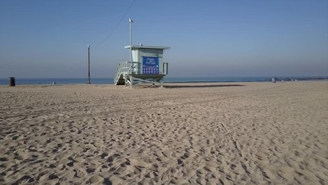 Lifeguard Tower at Venice Beach LA seagulls and surfers in aerial drone view. 4k shot of sand and waves in pacific ocean. Sunny morning in Los Angeles, California