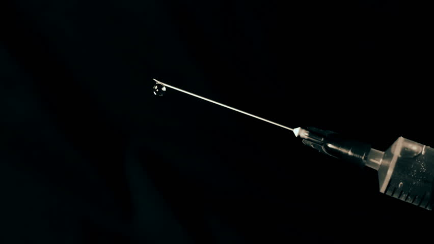 Medical syringe with liquid on black background. Water drop from syringe needle.  | Shutterstock HD Video #1021168645