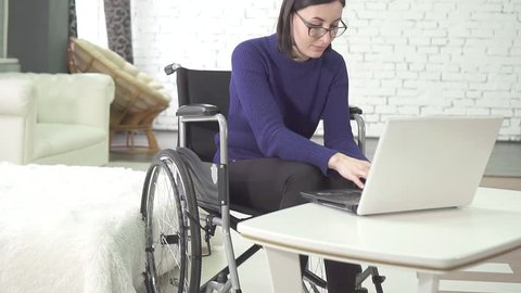 young disabled woman with glasses in a wheelchair chair with a laptop at home,smiling