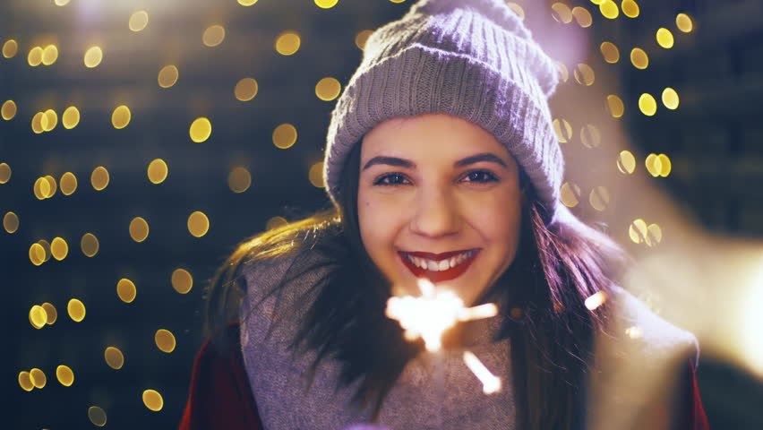 Girl with a sparkler enjoying time for Christmas 4K. Portrait sliding shot of young woman in focus wearing winter clothes and surrounded by decorative lights. | Shutterstock HD Video #1021189855