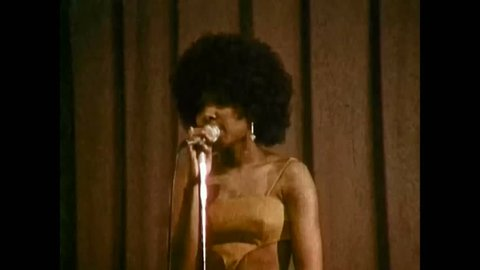 CIRCA 1970s - An African American singer, female, sings with the U.S. Navy Band, on a stage, in 1974.