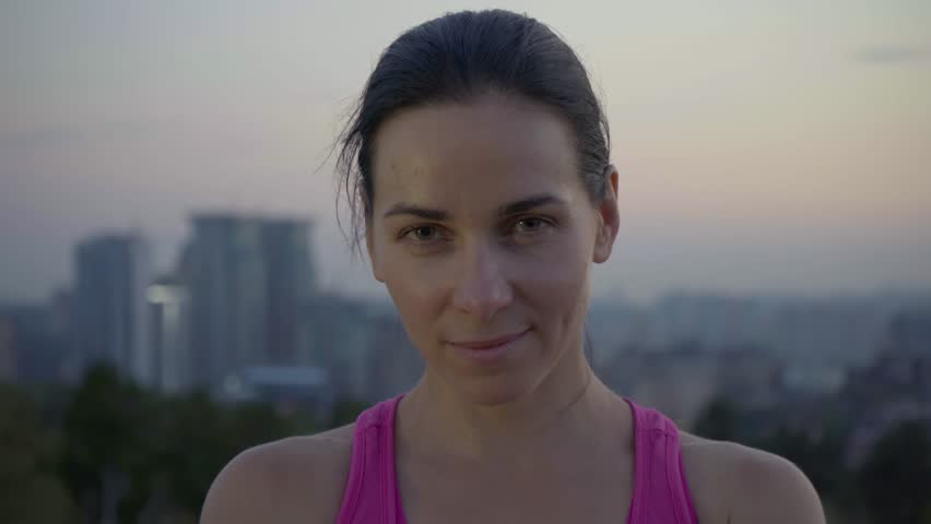Portrait of an attractive sportswoman on the background of the city. Cute young woman with a sporty build is looking at the camera. Long-haired brunette posing against the backdrop of the sunset away | Shutterstock HD Video #1021298635