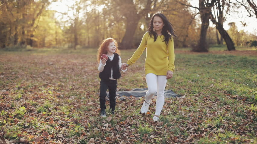 Happy young mother and her little redhead daughter walking together in an autumn park. They laughing and having fun holding hands. Slow motion #1021341685