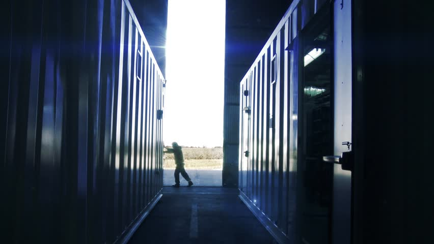 Man Opening Door of a Container Warehouse. Sun Flares Entering in the Back.  | Shutterstock HD Video #1021399225