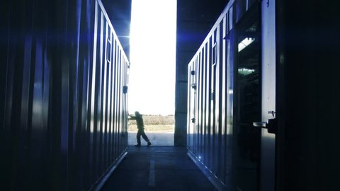 Man Opening Door of a Container Warehouse. Sun Flares Entering in the Back.