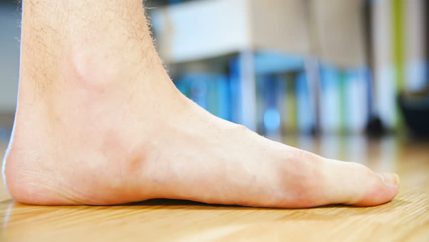Flat feet forcing arch up exercise close-up HD. Low angle view of person's foot in focus while lifting arch to make a healthy foot. Home dining room in the background out of focus. | Shutterstock HD Video #1021410775