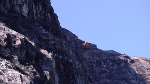 Man diving down in a wing suit in the mountains of Norway, Slow motion.