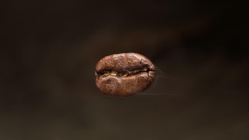 The flying macro coffee bean is steaming. Macro shot. Below is a blurred coffee background.
