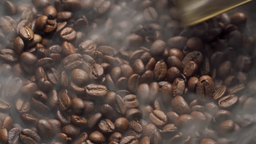 Fragrant coffee beans are roasted in a frying pan, smoke comes from coffee beans. The whole composition scrolls slowly around the camera. Scoop stir coffee beans.
