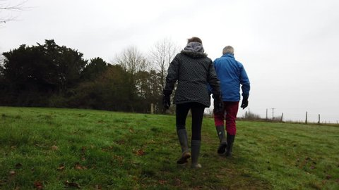 A heterosexual mature couple walk together through English countryside