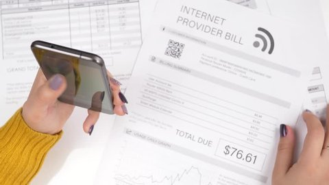 Paying bills using a mobile smartphone device. Online utility bills payment concept.The information on the bills are fake, placeholder name is use.