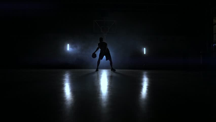 A man with a basketball on a dark basketball court against the backdrop of a basketball ring in the smoke shows dribbling skills illuminated by three lanterns in backlight | Shutterstock HD Video #1021511815