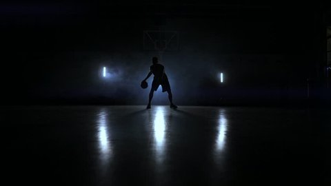 A man with a basketball on a dark basketball court against the backdrop of a basketball ring in the smoke shows dribbling skills illuminated by three lanterns in backlight