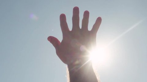 Close-up of hand reaching for sun. Stock. Bright sunlight breaks through fingers of outstretched hand to sky
