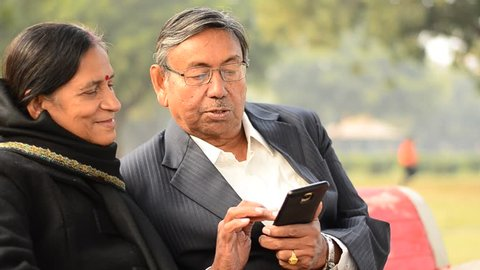 Senior citizen couple reading from / working on a mobile, reading jokes and talking, smiling, laughing  in a park in Delhi, India