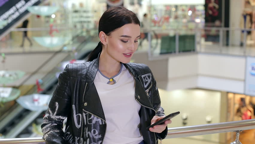 5354683308df Close-up of a fashionable cheerful girl in a leather jacket with the phone  in a large bright shopping center.