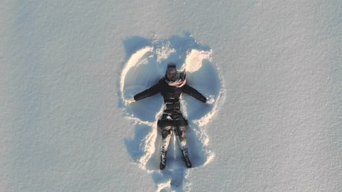 Top aerial view of young happy smiling girl making by arms snow angel figure and lying in snow, winter outdoor activity concept