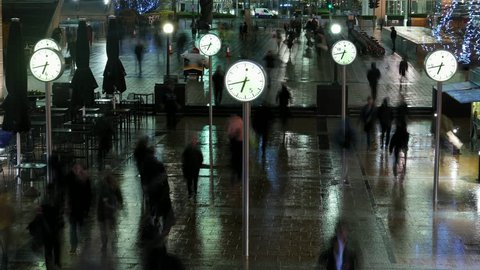 Businessmen and Commuters Walking by Public Clocks in Canary Wharf, London. Time Lapse