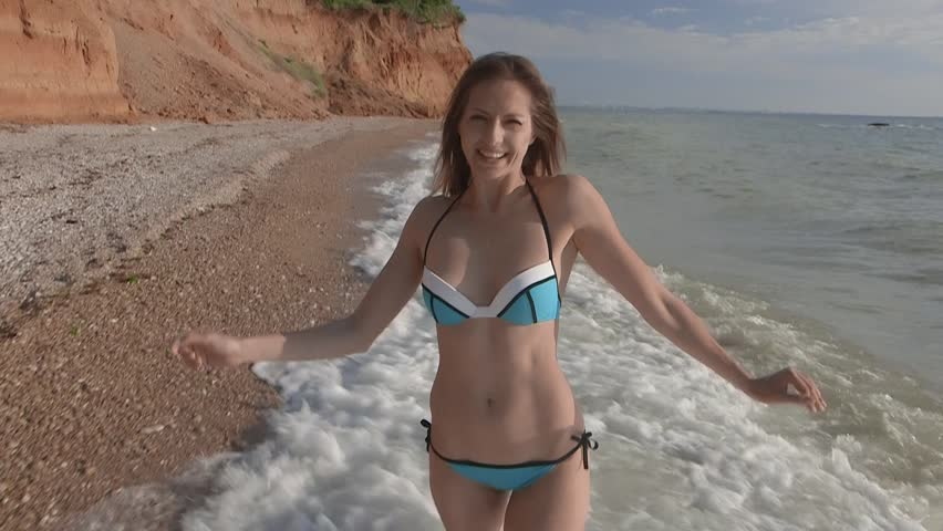 Young Beautiful Tanned Girl In Bikini With Sport Body Flat Stomach Walking On Water Cross Wave Sea Beach Smiling Enigmatically Touching Her Hair