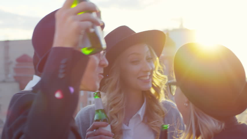 Two young beautiful women and Caucasian man in fedora hats smiling and dancing with beer bottles at party while multiethnic men talking in the background on rooftop
