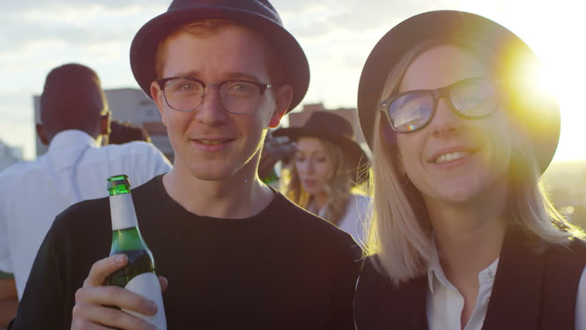 Young man and woman in fedora hats holding beer bottles, smiling and looking at camera while dancing together at rooftop party with multiethnic friends