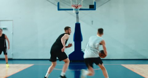 High school team playing basketball indoors, practicing combinations and drills. 4K UHD