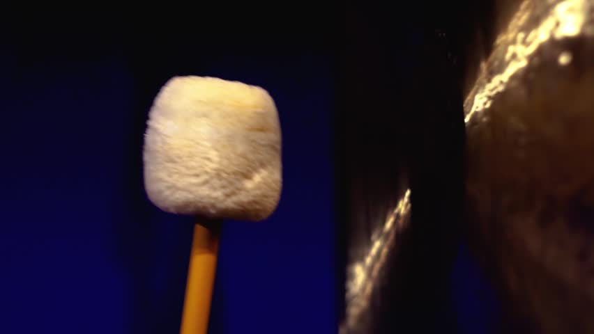 Gong mallet close-up hitting a big gong with in a dark room. Sound therapy. Mindfulness, tranquility and harmony.