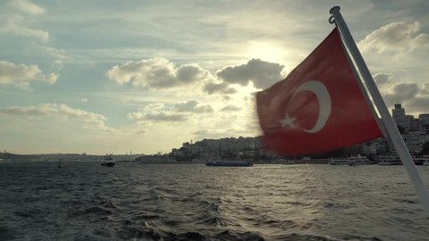 Vivid Red Turkish Flag Flutter On Wind Against, Stern Of Ferry Boat.Turkish Flag On Side Of Boat.Flag On Boat Ship In The Wind in Istanbul at Sunset.Red flag on a boat.Red Turkish Symbol Flap On Wind.