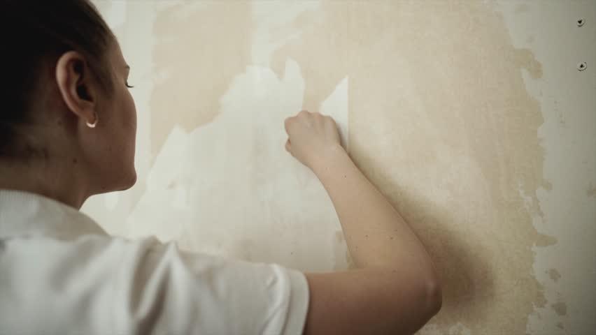 hand scrapes wallpaper off walls