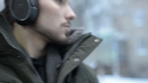Close up portrait Young long haired bearded man in a jacket and large headphones sits in public transport by the tram by the window and listens to music or an audiobook in the winter