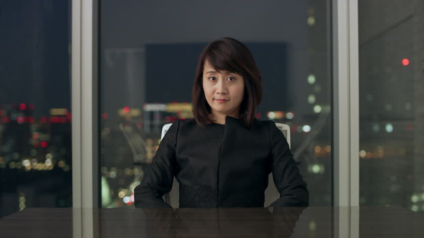 Professional Japanese woman sitting at a conference table in front of a large window with a view of night time in a conference room with soft interior lighting.