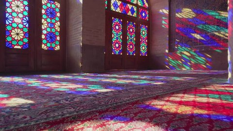 Shiraz, Iran - 29 October, 2018: Morning sunlight reflected through colorful stained glass windows on the wall and the floor of prayer hall of the Nasir al-Mulk Mosque (Pink Mosque). Bottom view.