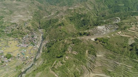 Aerial view rice terraces and agricultural land on slopes mountains. Village farmers near rice fields in mountain valley. Mountains covered forest, trees. Cordillera region. Luzon, Philippines.