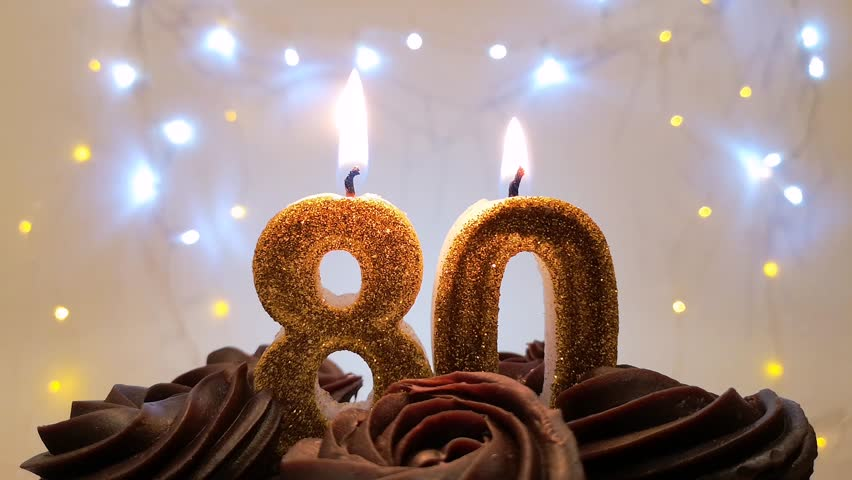 Burning Birthday Candle On A Cake Number 80 Blow Out At The End Color Blurred Background
