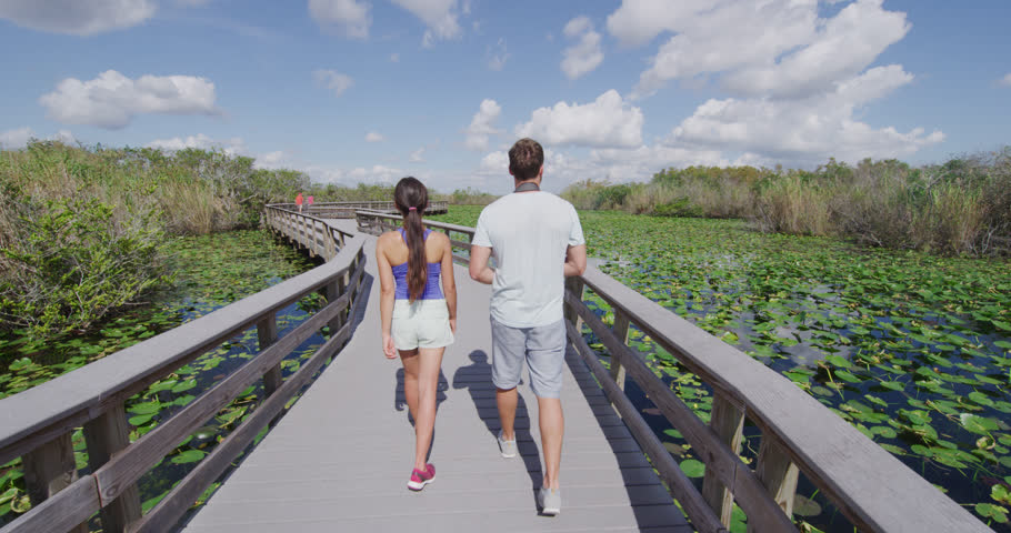 Everglades National Park Trail - tourists visiting Florida Everglades. Couple on travel in Miami doing day tour to Everglades walking Anhinga Trail. RED EPIC SLOW MOTION.