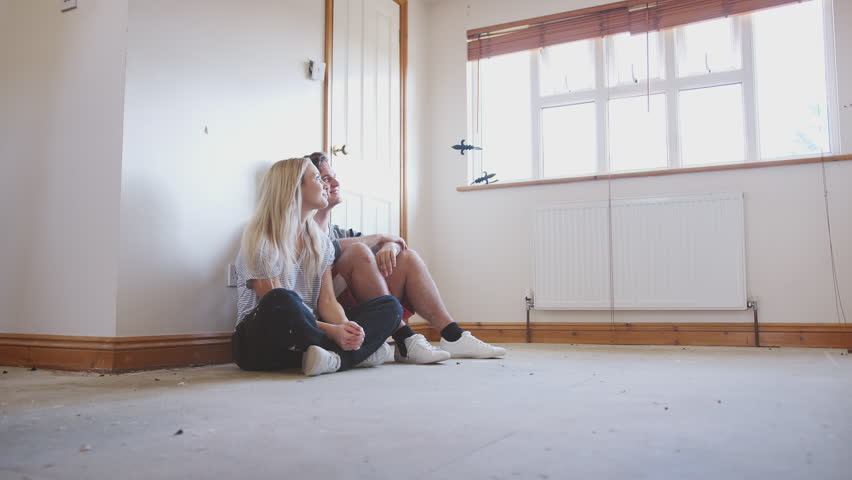 Couple Sitting On Floor In Empty Room Of New Home Planning Design   Shutterstock HD Video #1021969345