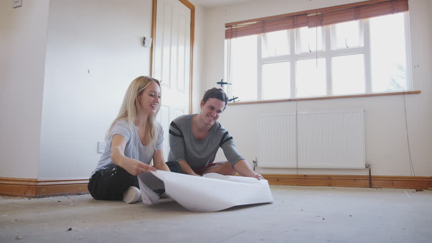 Couple Sitting On Floor Looking At Floor Plans In Empty Room Of New Home | Shutterstock HD Video #1021969375